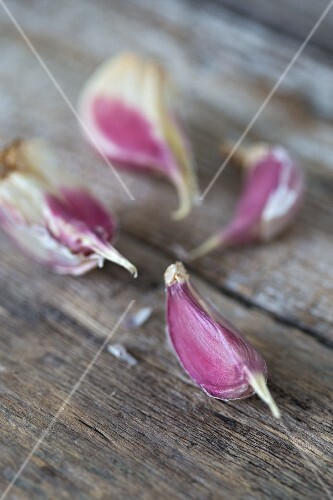 Four garlic cloves on a wooden surface (close up)