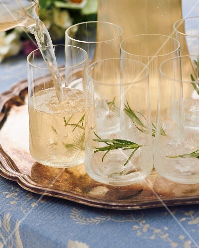 A rosemary drink being poured into glasses