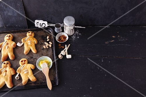 Bread men with almonds on a baking tray