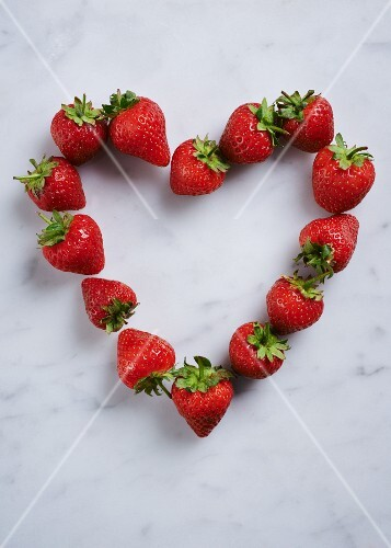 A heart of fresh strawberries on a white surface