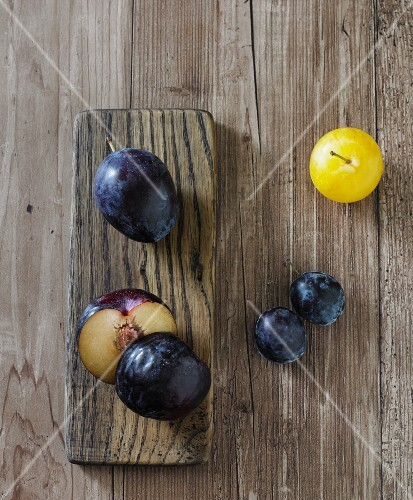 Various plums (black plums, a yellow plum, Italian plums)