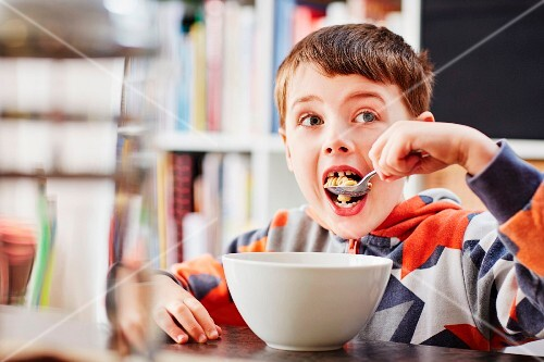 A boy eating a bowl of muesli