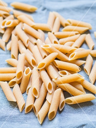 Wholemeal penne pasta on a blue cloth