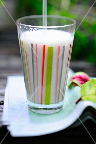 A glass of soya milk with a straw