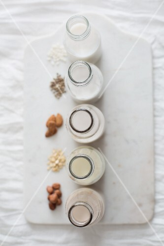 Bottles of rice milk, hemp milk, almond milk, oat milk and hazelnut milk next to ingredients