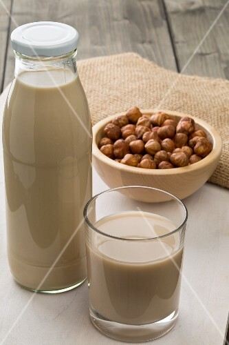 Hazelnut milk in a glass and a bottle with a bowl of hazelnuts