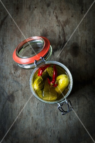 Gherkins with chillis in a preserving jar on a wooden table