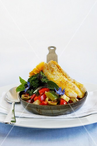 Baked fish fillet served with vegetables in a small pan