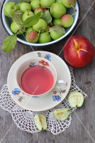 A cup of fruit tea and fresh fruit