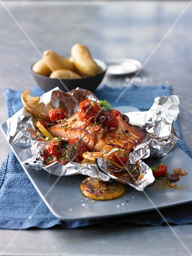 Mediterranean salmon fillet with cherry tomatoes and lemons cooked in foil