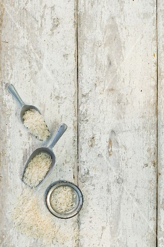 Rice in a bowl, on scoops and on a wooden surface