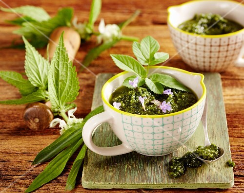 Wild herb pesto in a cup on a wooden board