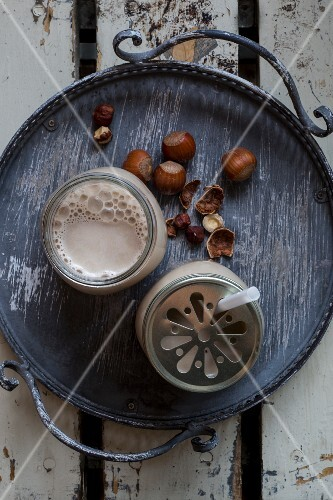 Vegan hazelnut milk in glasses with lids on a tray