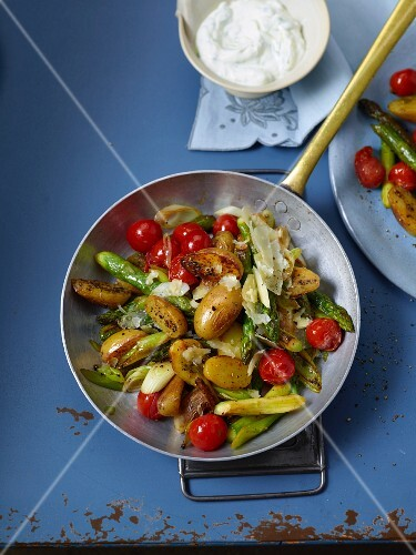 Fried potatoes with green asparagus and cherry tomatoes