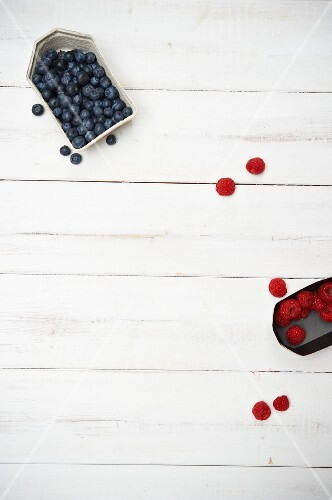 Blueberries and raspberries on a white wooden surface