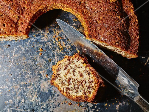Sliced rum and nut cake with a knife on a baking tray
