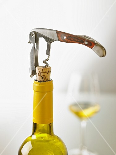 a bottle of white wine being open with a sommelier knife stockfood. Black Bedroom Furniture Sets. Home Design Ideas