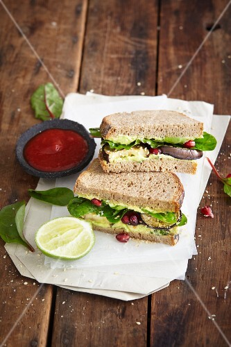 An avocado sandwich with pomegranate seeds and spinach