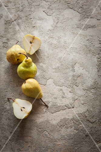 Pears and pear halves on a grey surface