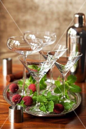 Empty cocktail glasses on a tray surrounded by fresh mint and lychees