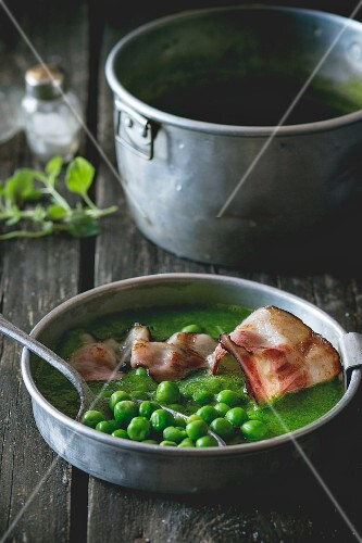 Cream of pea soup with fried bacon on a wooden table