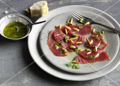 Tuna fish carpaccio with a parsley vinaigrette and pine nuts