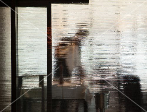 A waiter behind a glass wall in a restaurant