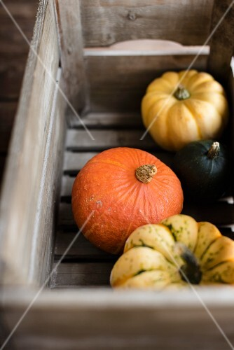 Various pumpkins in a wooden crate