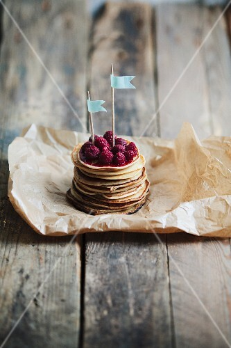 A stack of mini pancakes with raspberries and little flags