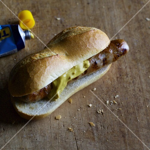 Homemade Munderland sausage with mustard in a roll