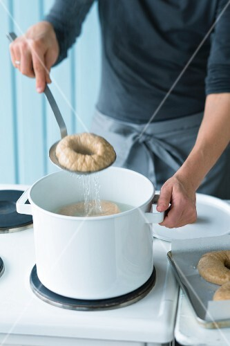 A bagel being removed from boiling salt water