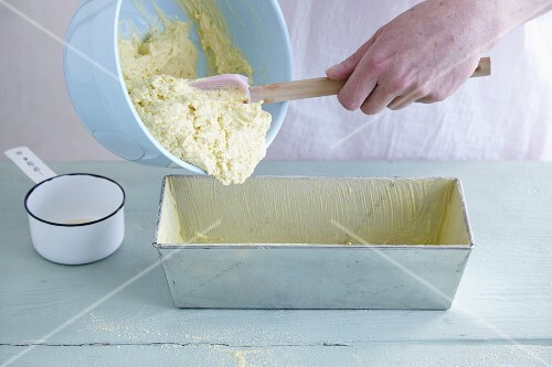 Gluten-free cake mixture being transferred to a loaf tin