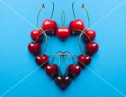 A digital composition of mirrored images of a cherry heart