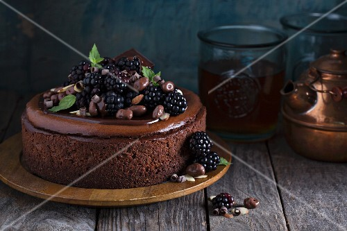 Chocolate cheesecake with blackberries on rustic wooden surface