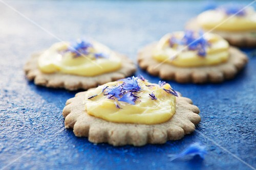 Shortbread biscuits topped with lemon curd and cornflowers on a blue surface