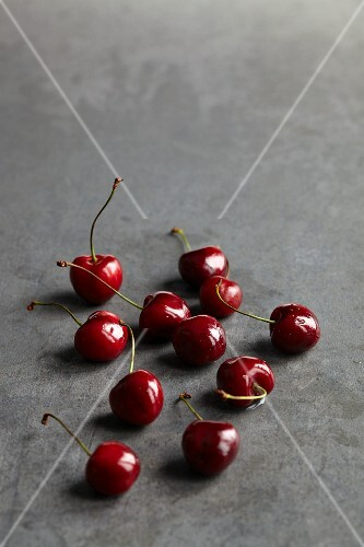 Red cherries scattered on a grey stone surface