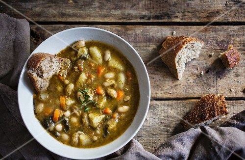Tuscan bean soup on a wooden surface with wholemeal bread