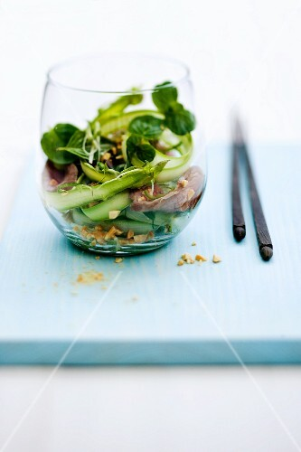 Spicy-sour asparagus and lamb fillet salad with peanuts and peppermint in a glass