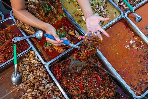 A street kitchen serving various curries at a market in Bangkok, Thailand