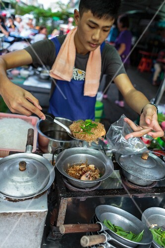 A young man transferring a prawn noodle dish into a bag, Bangkok, Thailand