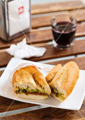 A baguette sandwich and a glass of red wine