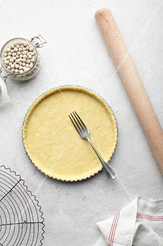 Making a tart: shortcrust pastry base being stabbed with a fork for blind baking