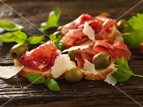 Bruschetta topped with Bresaola, green olives and Parmesan shavings