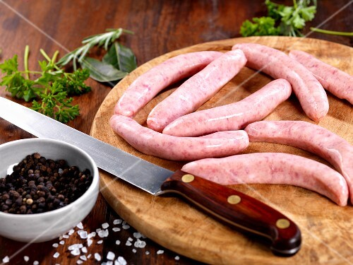 Raw sausages on a chopping board