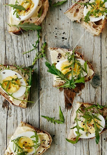 Slices of bread topped with egg and rocket