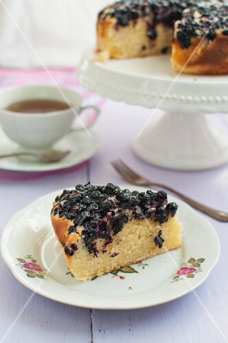 A slice of blueberry cake with icing sugar served with a cup of tea