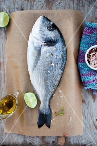 Gilt head seabream with olive oil, limes and Himalayan salt on a piece of baking paper