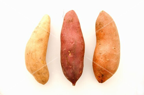 Three types of sweet potatoes on a white surface