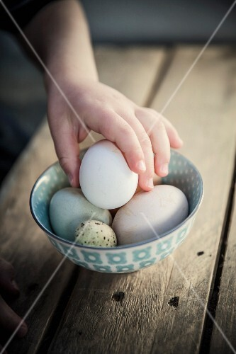 A child taking an egg from a bowl