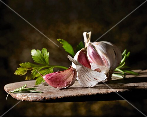 A garlic bulb and flat-leaf parsley on a wooden board